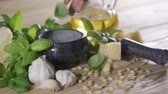 nourish : Human hand puts several cloves of garlic on the table. Ingredients for a sauce pesto.