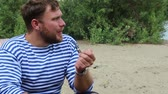 прибрежная полоса : sailor smoking a pipe, sitting near the water