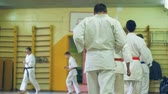 dövüş sanatları : Russia, Novosibirsk, August 15, 2018 A group of people practicing karate strokes indoors. Endurance training in karate