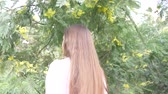 springtide : girl teenager straightens her long hair. she stands by the flowering mimosa tree. 4k, slow motion Stock Footage