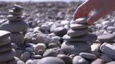 rochoso : close-up, hand folds a pyramid of stones on the seashore. 4k, slow motion