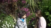 irmãos : two cute teen boy and girl talking in a blooming spring park. 4k, slow motion