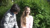 korkuluk : two cute teen boy and girl talking in a blooming spring park. 4k, slow motion