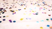 deriva : slow motion. 4k. round multicolored confetti lie on the tiled floor. dolly shooting