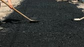 pavimentação : Road worker leveling fresh asphalt during asphalt pavement repair or construction works