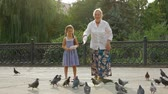 pomba : A child and an old lady feeding wild birds in a park