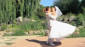 flirting : Bride and groom in a park on the wedding day Stock Footage