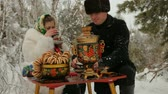 flirting : Young couple sitting in the winter in the woods and drink tea. Stock Footage