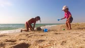 game : Two Children Building Sand Castle On The Beach