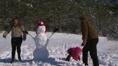 легко : Dad, mother and little daughter make a snowman in the meadow near the forest.