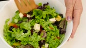 de baixa caloria : Female hands mix the salad in a large white bowl.