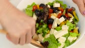 finely : A woman prepares a Greek salad of vegetables and cheese with olive oil.
