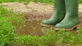 lodo : feet in rubber boots fun to jump across the puddle