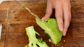 hands to cut broccoli into slices