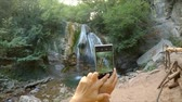 Hands make a photo of a waterfall on the phone.