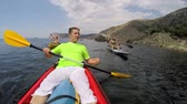 стиль жизни : Three people in kayaks on the sea