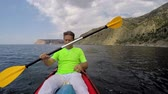 man swims into the sea in a kayak