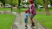 мясистый : A girl is jumping with a boy in a puddle.