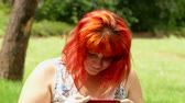 obrazy : Red-haired girl sends off her photo via smartphone