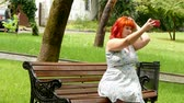 мясистый : Red-haired girl doing selfie on a park bench