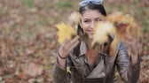 Woman drop up leaves in autumn park. Happy woman throwing leaves. Stock Footage