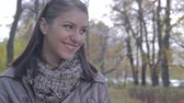 autumn : Woman smiles in beautiful autumn park landscape.Smiling brunette outdoors. Closeup of a beautiful smiling young woman.Young woman smiling and enjoying autumn sunshine.Beautiful young woman looks at the camera and smiles. Close up shot.