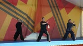 balances : Moscow, Russia - May 14, 2017: group of three wushu sportsmen performing together during the festival of martial arts One in the field is warrior.