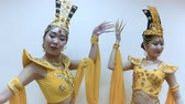 Two beautiful asian women dancing with hands with long nail manicure in a traditional thai yellow dress