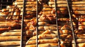 eats : Chicken pieces roasting on the grill over the fire.