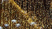bulbo : Yellow garland with a lot of light bulbs hanging on the street