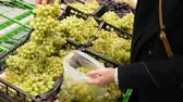 raflar : woman in supermarket selects the grapes, 4K