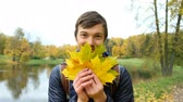 выглядывал : Young cheerful man peeking from behind yellow maple leaves and smiling looking at camera closeup Стоковые видеозаписи