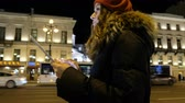 Центральный район : Young beautiful girl with tablet is at the bus stop and waiting for the bus in the evening city