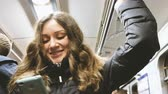 correspondência : Young beautiful girl with a smartphone in the hands of rides on the subway. Smiles and looks at the screen, going to friends for a party.