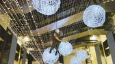 sestup : Industrial climber mounts Christmas decorations in the unsupported space in the shopping center Dostupné videozáznamy