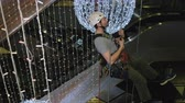 альпинист : Industrial climber mounts Christmas decorations in the unsupported space in the shopping center Стоковые видеозаписи