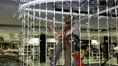 alpinista : Industrial climber sets up Christmas decorations in the shopping centre