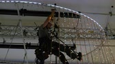 kask : Industrial climber mounts Christmas decorations in the unsupported space in the shopping center Wideo