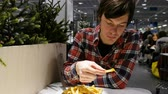 jídelna : Young man eating French fries at the food court of the shopping center, 4k. Dostupné videozáznamy