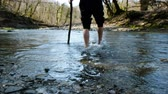 gázló : A young man crosses a mountain river wade barefoot with a stick, 4k.