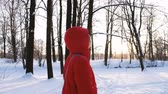 fadas : A girl in a red down jacket walks in the woods in winter at sunset, slow motion