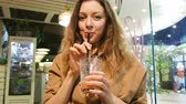 elegante : Young girl offers to drink smoothies from the tube in a cafe Stock Footage
