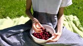 кудри : European girl eating ripe sweet cherry in nature from a plastic container