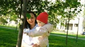 piknik : Happy mother holds a child in her arms in a city park. Baby is playing with a leaf on the tree at sunset.