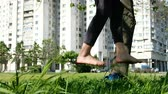 slackline : European girl is walking on a tight line in a city park. Woman balancing on slackline, close-up