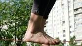 slackliner : Woman legs walk along a tight line in a city park. Foot woman balances on the slackline side