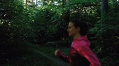 olympic park : Young girl runs in the forest, a woman is running in the park in summer, slow motion of the camera. Close up