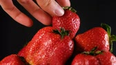 iştah : Woman puts one strawberry on top of a big pile on a dark background, close-up