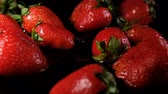 темно бордовый : Strawberry falls into the water on a dark background, slow motion Стоковые видеозаписи