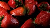 édes : Strawberry falling into the water on a dark background, slow motion